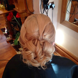 Beautiful golden blond hair pulled in and placed with grips through the top to create softness and movement then curled and secured in barrels curls through the back  to achieve a secure formal hair up do. Perfect wedding hair. Back.