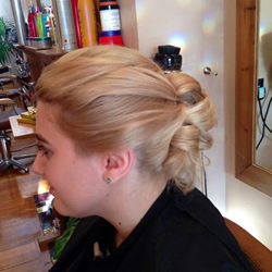 Beautiful golden blond hair pulled in and placed with grips through the top to create softness and movement then curled and secured in barrels curls through the back  to achieve a secure formal hair up do. Perfect wedding hair. Left Profile.