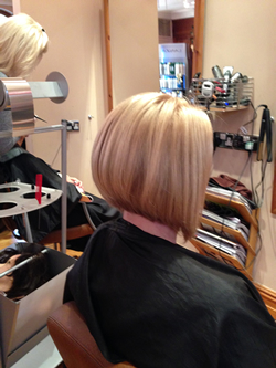 Regrowth tint to cover natural hair growth with subtle foil highlight weaves through top section to create sun kissed tones. Cut into the nape and dropping longer towards the front for a graduated bob style. Back right.