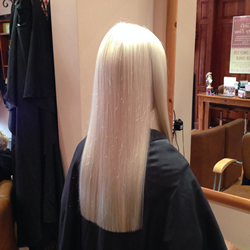 Long hair with one length cut adds thickness to the style, and some shape around the front creates softness. Ghd irons were also used to smooth the hair and complete the finished look. Back View