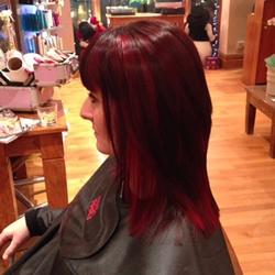 Full head permanent dark brown hair colour with really vibrant red slices in foils through to add texture, left profile view