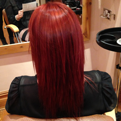 Blonde lady after getting her hair coloured red at the hair and beauty centre marple. Back angle