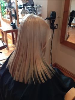 Stunning soft blonde achieved with a root application and a toner.. The light will show different shades making it look natural. Left at a medium length blunt cut on the ends and softened around the face with a side fringe. Back right view.