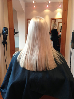 Stunning soft blonde achieved with a root application and a toner.. The light will show different shades making it look natural. Left at a medium length blunt cut on the ends and softened around the face with a side fringe. Back View